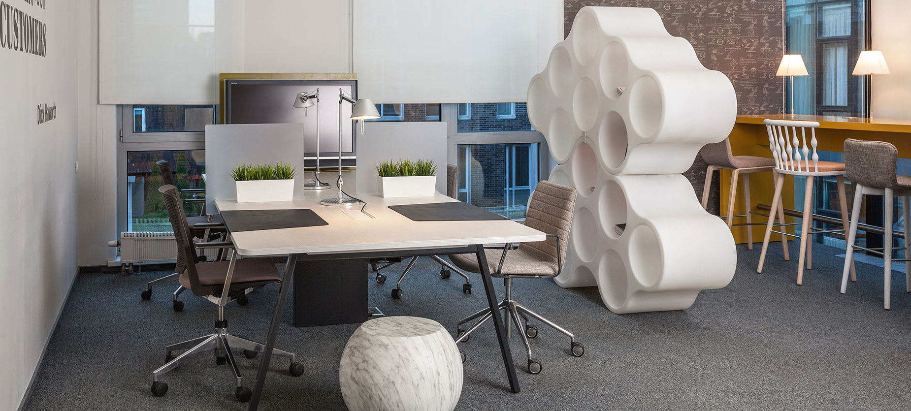 This hot-desking space features a four-person bench with movable screens and a display. Cloud storage serves as a space divider between desks and the bar table, which accommodates for sit/stand work.