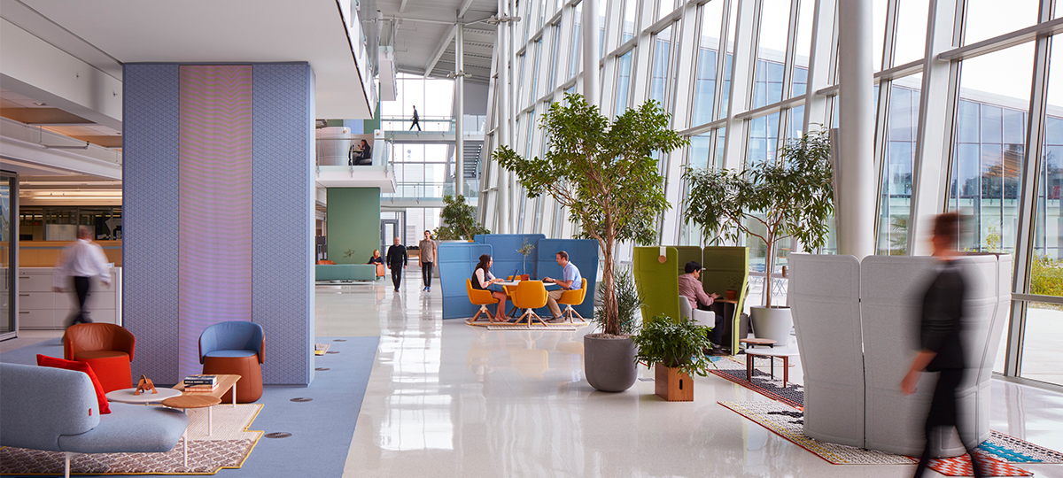 The use of screens, plants, and architectural features create space division and a sense of privacy in a large atrium volume, making this a place where people can comfortably connect.