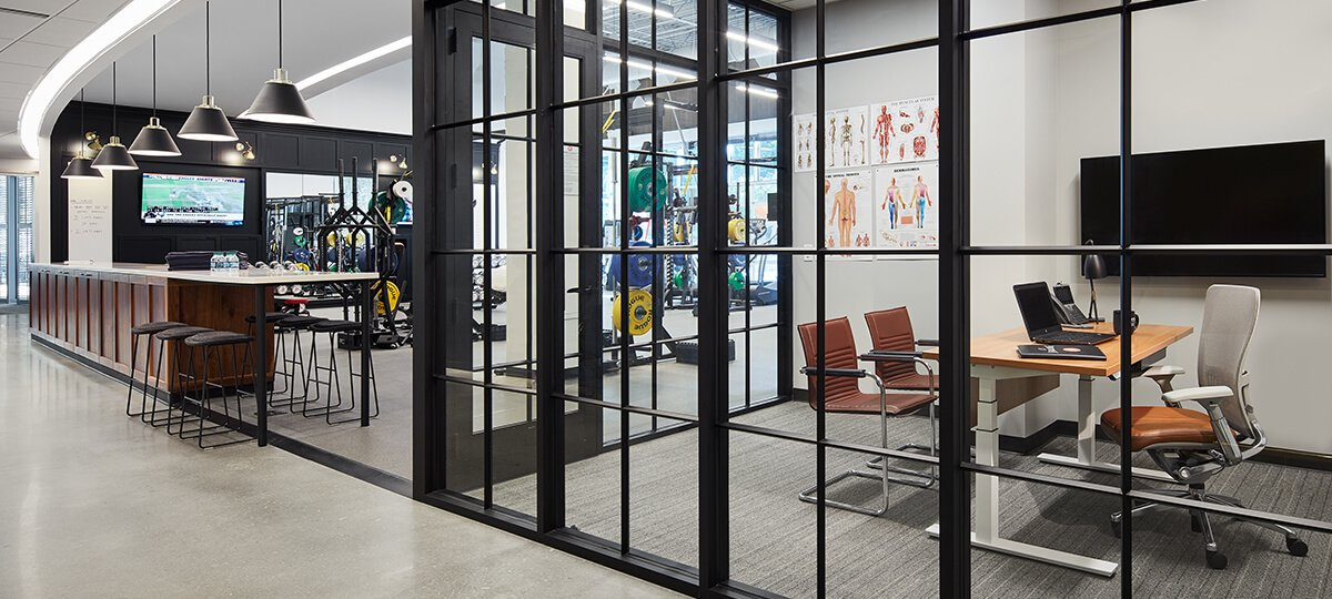 Attracting the best talent and a focus on health and well-being are two drivers behind the space design. This impressive training area highlights advanced weight-training equipment separated by a sleek black-accented glass wall. The training manager has visibility from his office behind the glass. A Planes® height-adjustable table, Exchange™ guest chairs, and a Zody® task chair provide functionality and comfort for athletes and their trainers in a small collaborative area used for relaxing, hydrating, or interacting. X Series® storage provides a solution for a variety of storage needs and requirements.